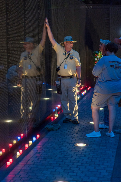 Volunteers assist visitors in locating names inscribed on the wall.