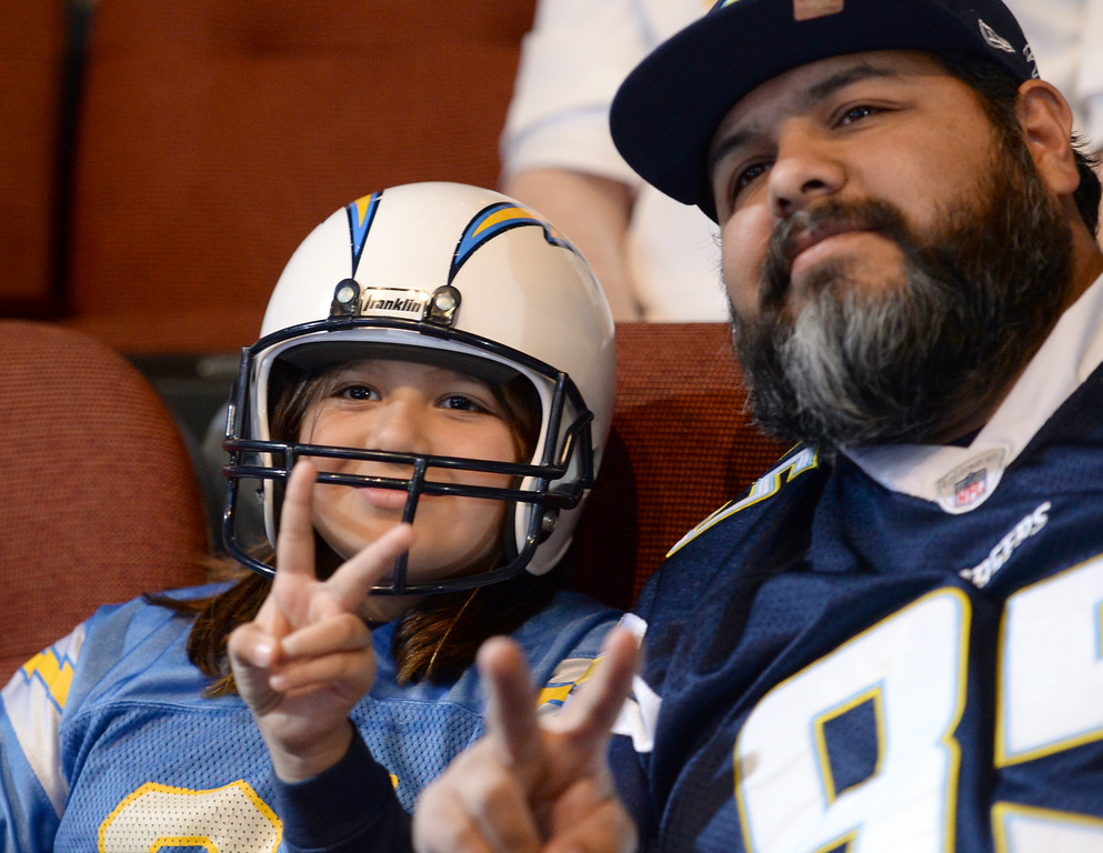 . Lily, 9,  and Luis Salas, of Inglewood, pose for a photo before a ceremony was held at the Forum to welcome the Los Angeles Chargers back Wednesday, January 18, 2017, Inglewood, CA.   In attendance was NFL Commissioner Roger Goodell, Chargers Chairman Dean Spanos,  quarterback Philip Rivers, coach Anthony Lynn and many others. Photo by Steve McCrank, Daily Breeze/SCNG