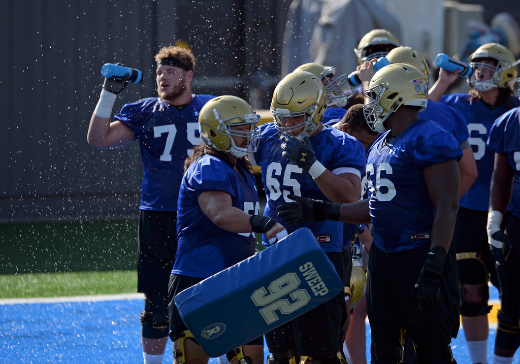 . UCLA offensive linemen, including Paco Perez (65) and Sunny Odogwu (66) take a water break during football practice at Spaulding Field on campus Friday, August 04, 2017, Westwood, CA.   (Photo by Steve McCrank, Daily Breeze/SCNG)