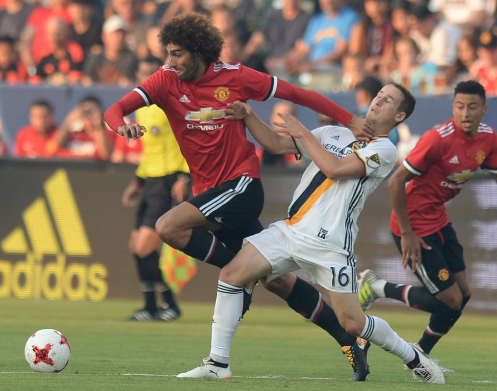 . Manchester United\'s Marouane Fellaini (27) fends off LA Galaxy\'s Nathan Smith (16) in an international friendly soccer game at the StubHub Center Saturday, July 15, 2017, Carson, CA.  Manchester led 3-0 at halftime. (Photo by Steve McCrank, Daily Breeze/SCNG)