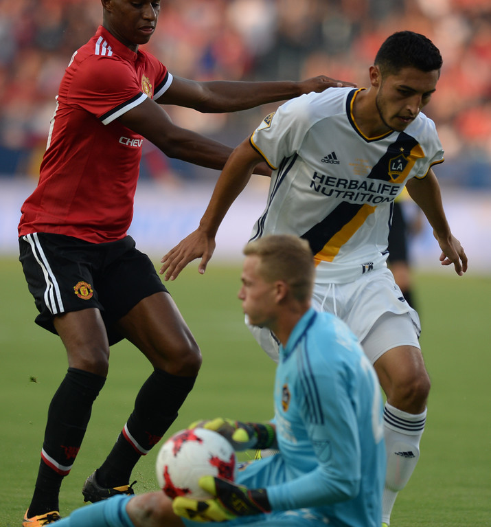 . LA Galaxy\'s keeper Jon Kempin (22) slides in to take the ball ahead of Manchester United\'s Marcus Rashford (19) and Galaxy\'s Hugo Arellano (21) in an international friendly soccer game at the StubHub Center Saturday, July 15, 2017, Carson, CA.  Manchester led 3-0 at halftime. (Photo by Steve McCrank, Daily Breeze/SCNG)