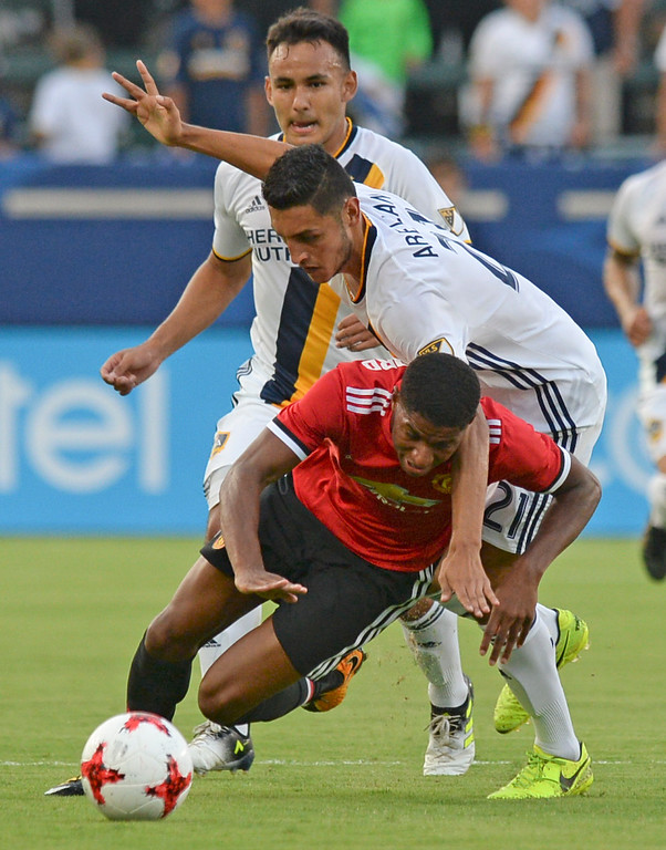 . Manchester United\'s Marcus Rashford (19) is taken down by  LA Galaxy\'s Hugo Arellano (21) in an international friendly soccer game at the StubHub Center Saturday, July 15, 2017, Carson, CA.  Manchester led 3-0 at halftime. (Photo by Steve McCrank, Daily Breeze/SCNG)