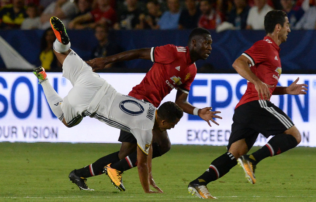 . LA Galaxy\'s Giovani dos Santos (10) is upended by Manchester United\'s Paul Pogba (6) in an international friendly soccer game at the StubHub Center Saturday, July 15, 2017, Carson, CA.  Manchester won 5-2. (Photo by Steve McCrank, Daily Breeze/SCNG)