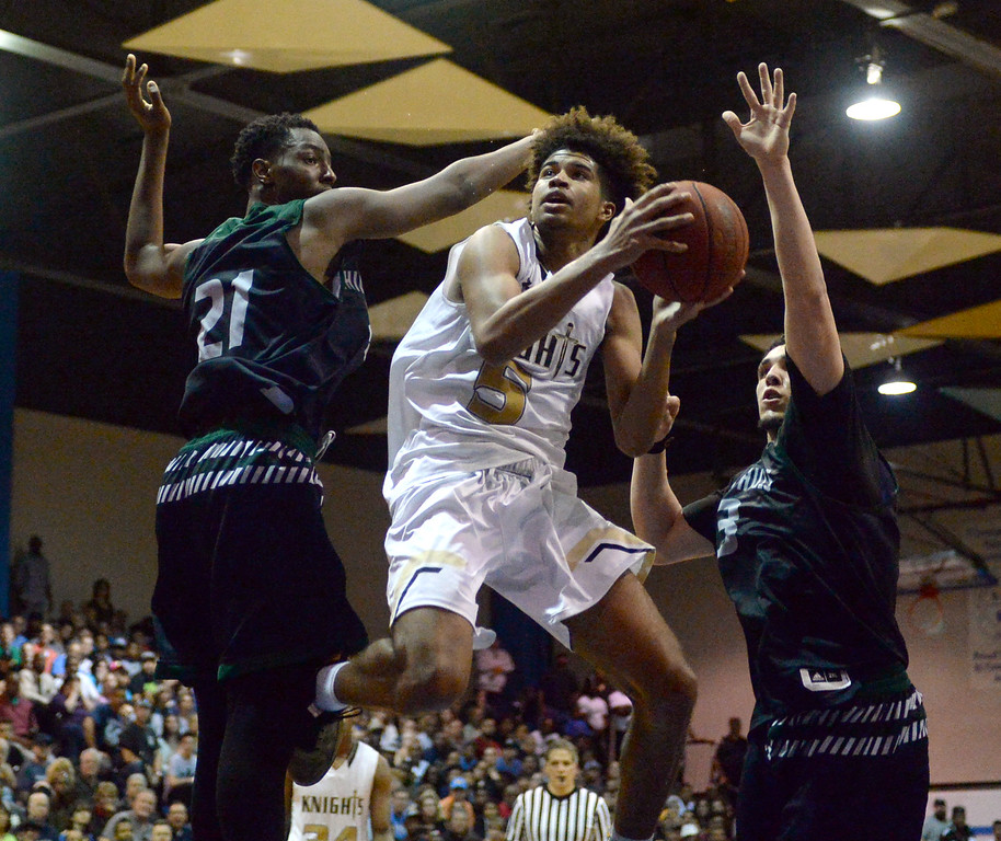 . Bishop Montgomery\'s Ethan Thompson (5) eyes the basket as he goes airborne through Chino Hills\' Onyeka Okogwu (21) and LiAngelo Ball (3) in a CIF State Open Division boys basketball game played at El Camino College Tuesday, March 14, 2017, Torrance, CA. Bishop Montgomery won 87-80. Photo by Steve McCrank, Daily News/SCNG