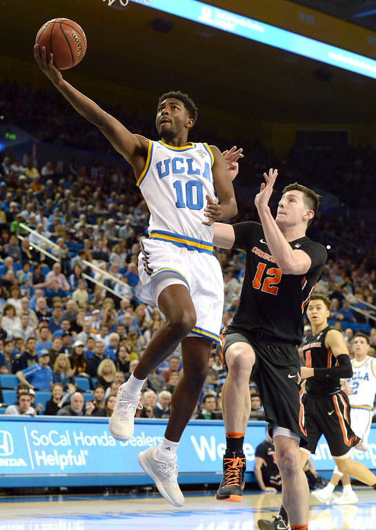 . UCLA\'s Isaac Hamilton (10) takes the ball into the basket past Oregon State\'s Drew Eubanks (12) in a PAC-12 men\'s basketball game at Pauley Pavilion Sunday, February 12, 2017, Westwood, CA.  UCLA led at the half 32-27. UCLA BRUINS vs. OREGON STATE BEAVERS Photo by Steve McCrank, Daily Breeze/SCNG