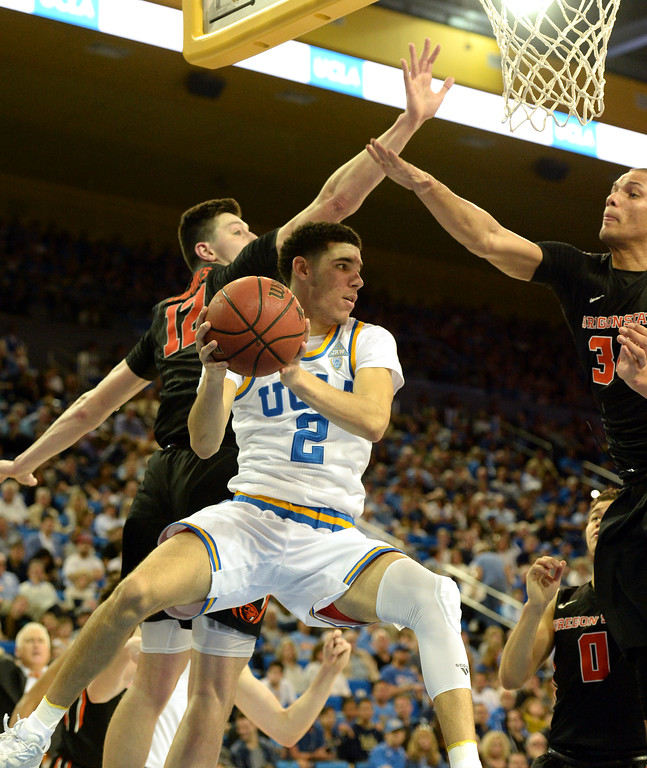 . UCLA\'s Lonzo Ball (2) drives to the basket and fakes a shot, passing through Oregon State\'s Drew Eubanks (12) and Ben Kone (34) in a PAC-12 men\'s basketball game at Pauley Pavilion Sunday, February 12, 2017, Westwood, CA.  UCLA led at the half 32-27. UCLA BRUINS vs. OREGON STATE BEAVERS Photo by Steve McCrank, Daily Breeze/SCNG