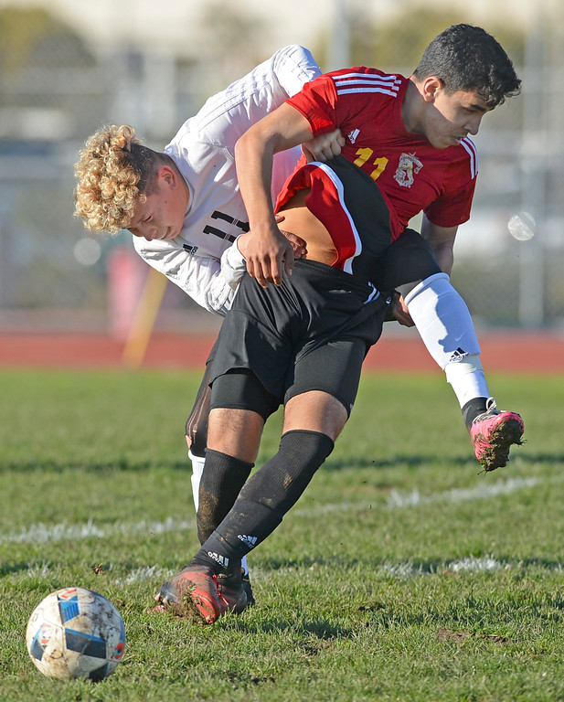 . Lawndale\'s Mario Perez (11) and Hawthorne\'s Adrian Hernandez (11) tussle in an otherwise gentlemanly  Ocean League soccer game Wednesday, January 25, 2017, Lawndale, CA.   Photo by Steve McCrank, Daily Breeze/SCNG