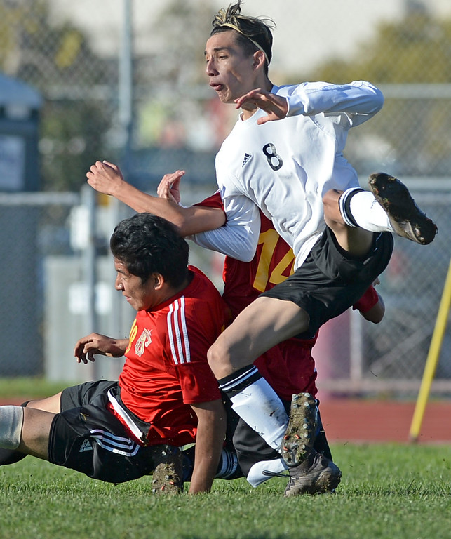 . Lawndale\'s Justin Islas (8) and Hawthorne\'s Cristian Martinez (18) and Jesse Carmona (14) all hit the dirt as they collide going for the ball in an Ocean League soccer game Wednesday, January 25, 2017, Lawndale, CA.   Photo by Steve McCrank, Daily Breeze/SCNG
