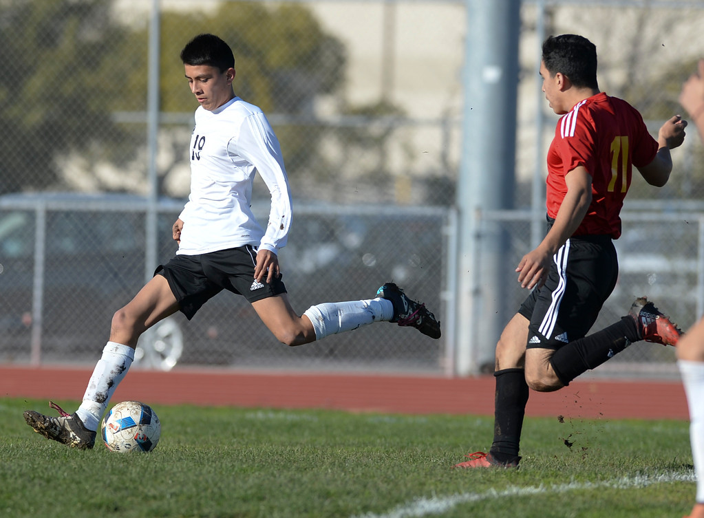 . Lawndale\'s Anthony Canseco (19) kicks a goal as he gets ahead of Hawthorne\'s Adrian Hernandez (11) in an Ocean League soccer game Wednesday, January 25, 2017, Lawndale, CA.   Photo by Steve McCrank, Daily Breeze/SCNG