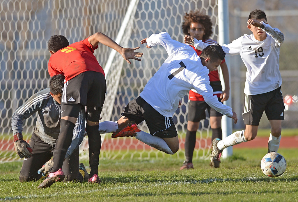 . Lawndale\'s Osvaldo Garcia (7) hits the ground after colliding with Hawthorne keeper Salvador Ontiveros (1) in an Ocean League soccer game Wednesday, January 25, 2017, Lawndale, CA.   Photo by Steve McCrank, Daily Breeze/SCNG