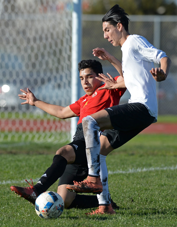 . Lawndale\'s Eduardo Casillas (17) tries to dodge a slide tackle from Hawthorne\'s Adrian Hernandez (11) in an Ocean League soccer game Wednesday, January 25, 2017, Lawndale, CA.   Photo by Steve McCrank, Daily Breeze/SCNG
