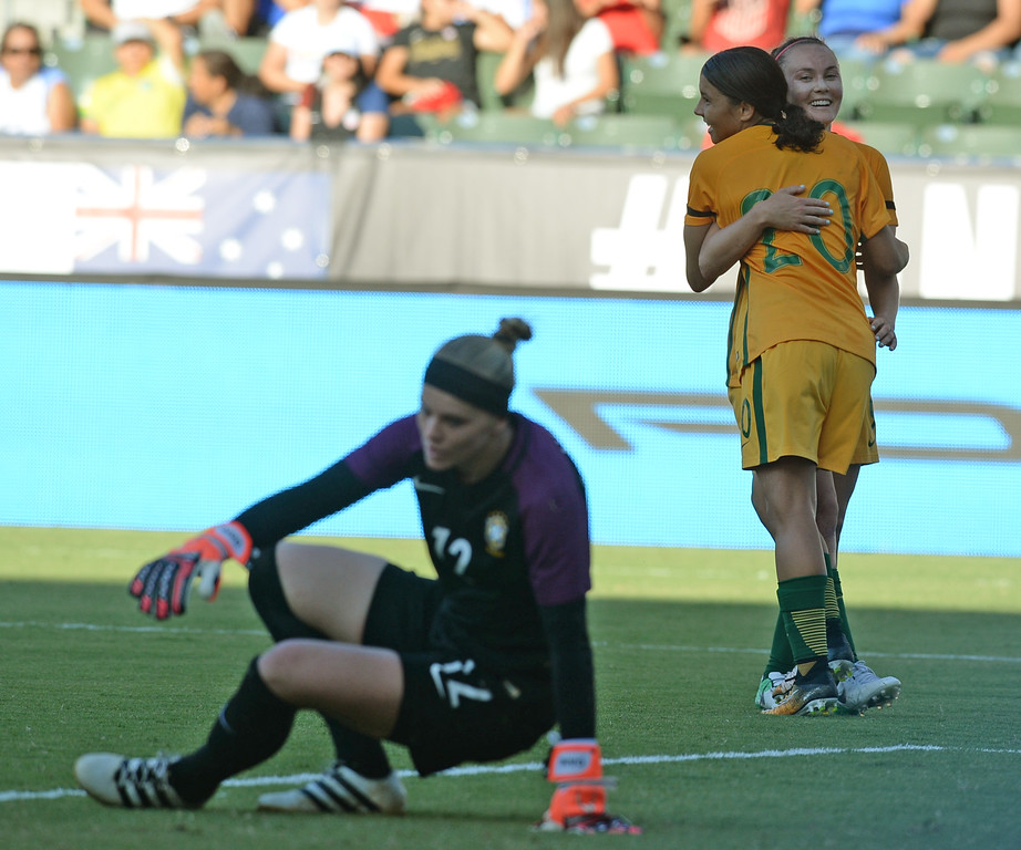 . Australia\'s Sam Kerr (20) and Caitlin Foord (9) celebrate a goal as Brazil\'s keeper Dani Neuhaus (12) gets off the ground in the final soccer game of the Tournament of Nations at the StubHub Center Thursday, August 03, 2017, Carson, CA.  Australia won 6-1 and the win gives them the tournament title. (Photo by Steve McCrank, Daily Breeze/SCNG)