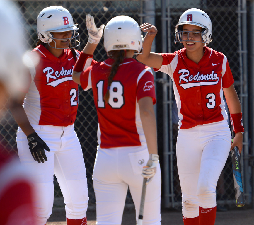 . Redondo\'s Amy Simonek (18) high-fives Jessie Rodarte (20) and Victoria Hamilton (3) after the two scored on Peninsula in a Bay League softball game Wednesday, April 19, 2017, Rolling Hills Estates. (Photo by Steve McCrank, Daily Breeze/SCNG)