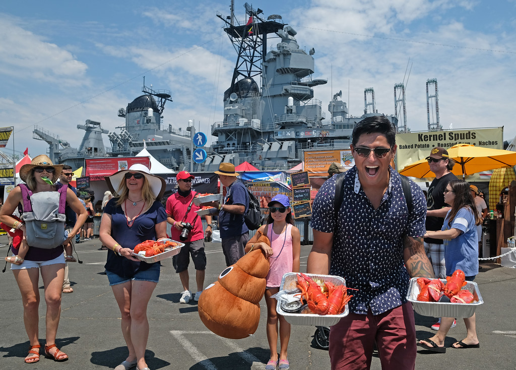 . The 19th Annual Port of Los Angeles Lobster Festival was held by the Battleship Iowa Saturday, July 15, 2017, San Pedro, CA.  Lobsterfest participants were able to purchase a Maine lobster and partake in a fairway, music, and shopping.  People are excited about their meals as they look for a shady place to sit. (Photo by Steve McCrank, Daily Breeze/SCNG)