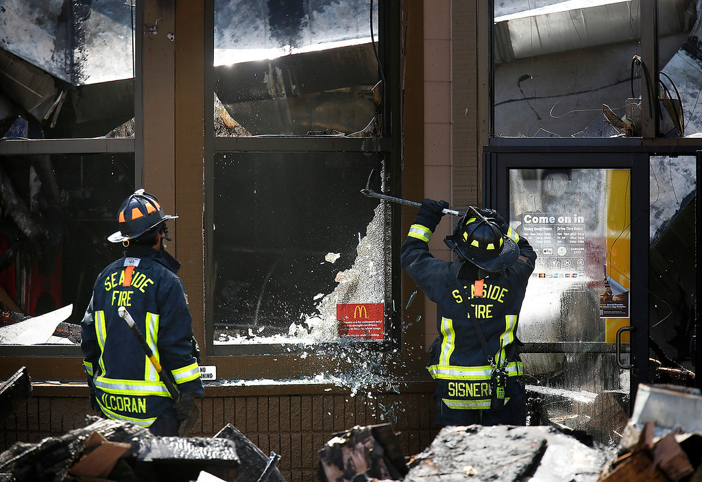 . Seaside Firefighters knock out glass near the front door of the burned out Macdonald\'s on Canyon Del Rey in Seaside on Tuesday June 5, 2018. (David Royal/ Herald Correspondent)