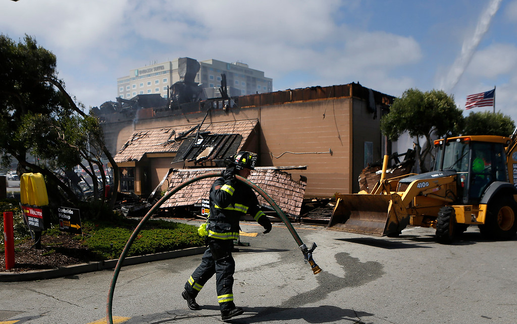 . Seaside reserve firefighter Nick Hall carries a hose as crews water down the burnt shell of Macdonald\'s on Canyon Del Rey in Seaside on Tuesday June 5, 2018. (David Royal/ Herald Correspondent)