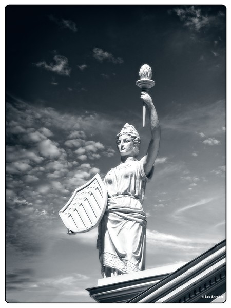 "Black and white film-look renderring of one of three statues of Lady Justice adorning the dome of the McLennan County Courthouse in historic downtown Waco, Texas. This  is said to be the Americanized version, featuring a shield and torch. Part of the courthouse design by architect James Riely (pronounced ""Riley""), a Texan who became one of the leading creators of courthouse and public building architecture in the United States. Raw development and procerssing in ON1 Photo RAW 2018.1 (Black & White: Ingrid Cool)."