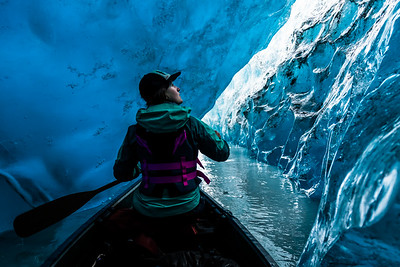 Woman looking up from canoe inside ice cave in Alaska