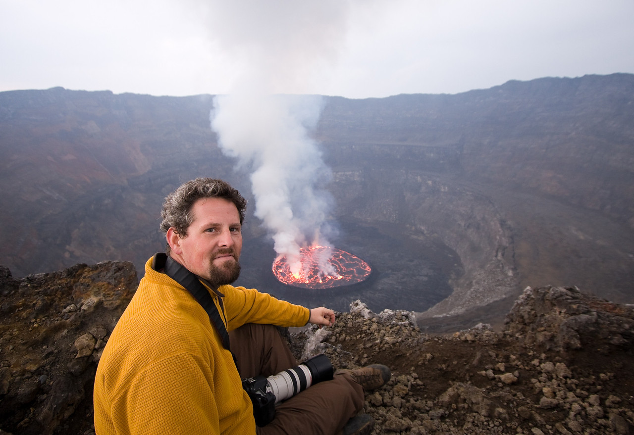 Located just outside of the western Congolese city of Goma, the Nyiragongo volcano contains one of the few permanent lava lakes on the planet (Wikipedia lists but 5).  Despite the precarious political situation in the DRC, a visit here isn't that difficult with a reasonably well developed visa- and permitting-process in place for visiting the country and the volcano, respectively and a fairly steep but manageable 6 hour hike from the park headquarters to the summit.<br /> <br /> Here, I sit on the rim overlooking the circular convecting pool below me.  As expected, it was a fantastic sight to behold.<br /> <br /> Location: Nyiragongo volcano, Goma, Democratic Republic of Congo (DRC)<br /> <br /> Lens used: 10-22mm f3.5-4.5