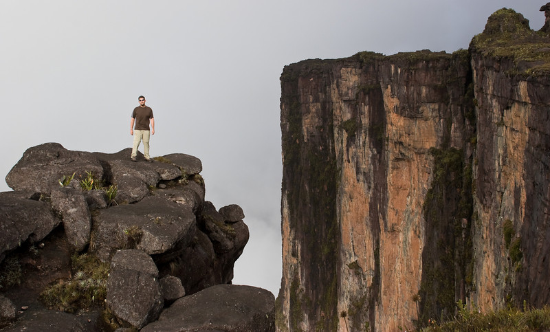 The tepui of Venezuela and Guyana contain some of the tallest cliffs on the planet, some up to 1000 meters (3200 feet) high. You're only seeing about 2/3rds of the full cliff in this photo.  They're really quite astonishing.  And scary.<br /> <br /> Here, I pose near the edge of one.<br /> <br /> Location: Mt. Roraima, Venezuela<br /> <br /> Lens used: 28-135mm f3.5-5.6 IS