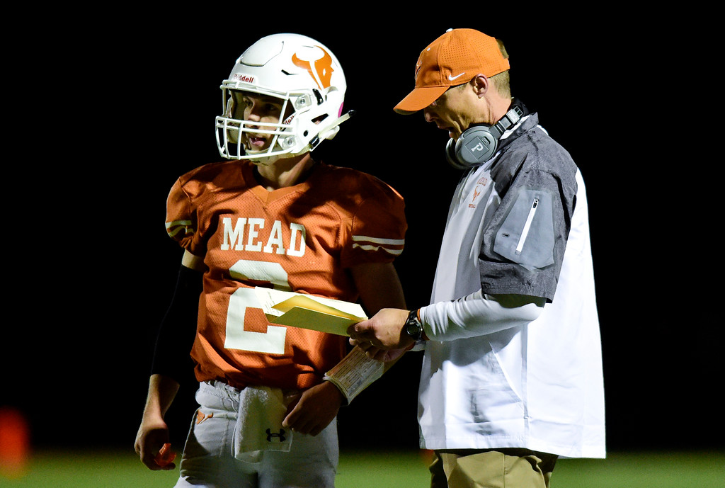 . Mead High School\'s head coach Jason Klatt talks with Tyler Keys (No. 2) during the game against Roosevelt High School in Mead, Colorado on Oct. 6, 2017.  (Photo by Matthew Jonas/Times-Call)