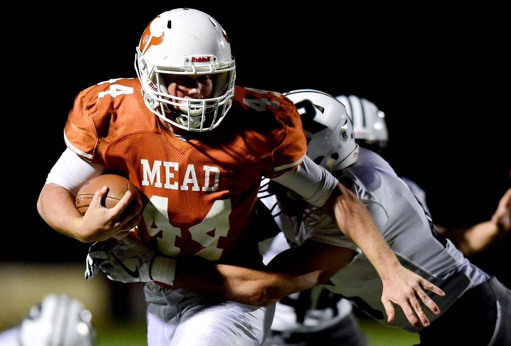 . Mead High School\'s Derek Edwards (No. 44) tries to shake a tackle from Roosevelt High School\'s Brandin Obrecht (No. 45) in Mead, Colorado on Oct. 6, 2017.  (Photo by Matthew Jonas/Times-Call)
