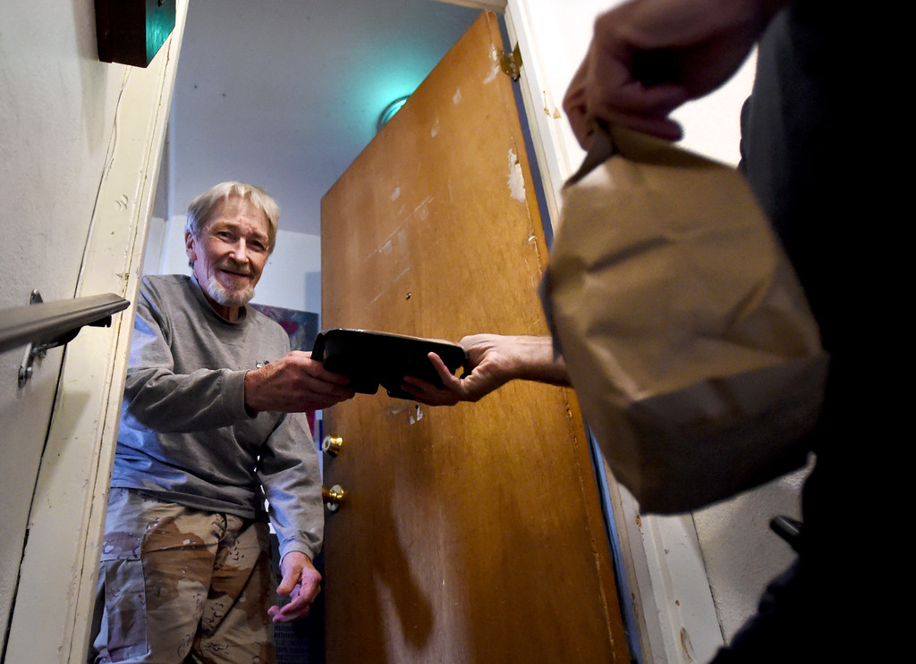 . Mike Small, right, a Meals on Wheels driver, makes a drop off to Stephen Miles on Wednesday.   Cliff Grassmick  Photographer November 22, 2017