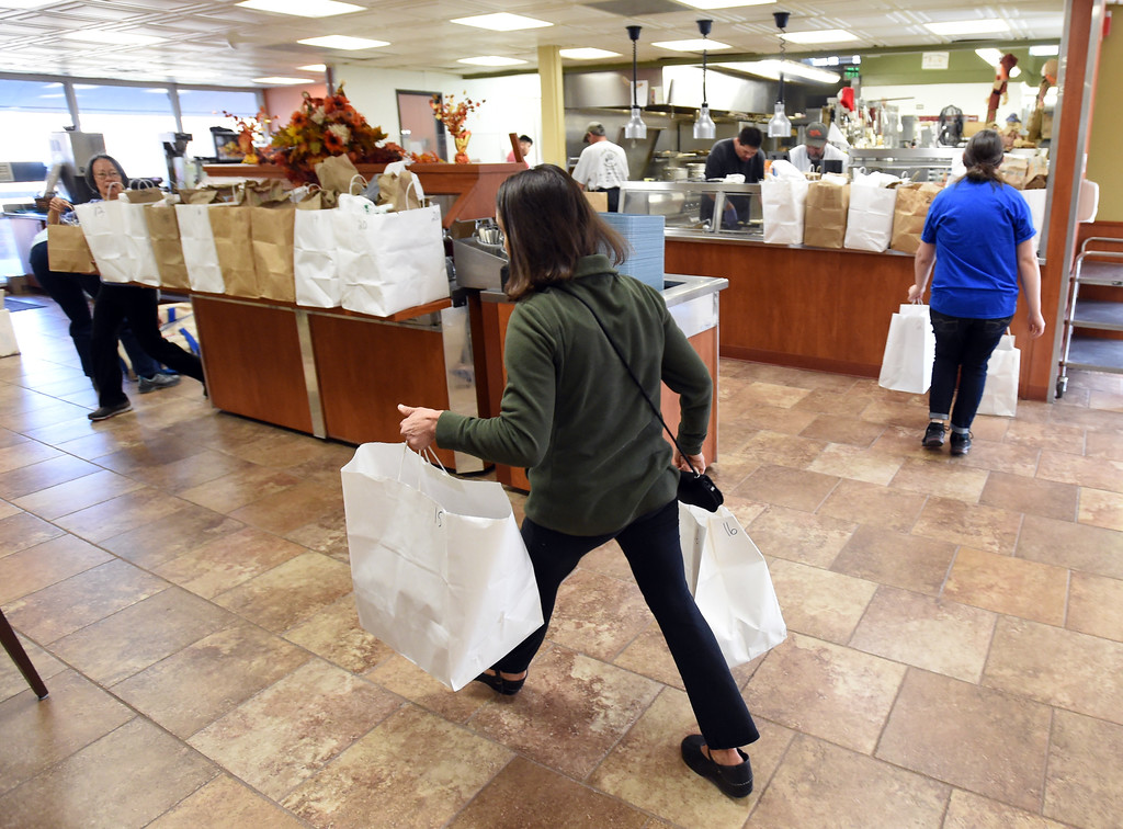 . Caroline Blecher takes bags to the driver pick up area at the West Seniors Center in Boulder.  Cliff Grassmick  Photographer November 22, 2017