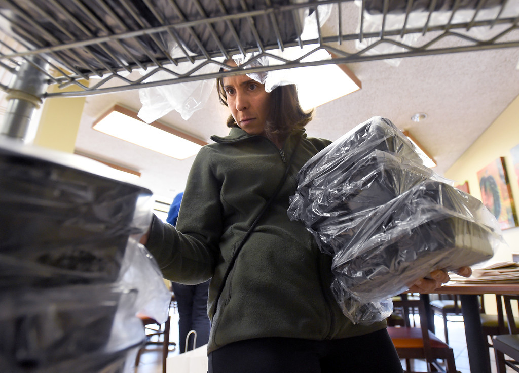. Caroline Blecher gathers up meals to be bagged for Meals on Wheels at  the West Seniors Center in Boulder.  Cliff Grassmick  Photographer November 22, 2017