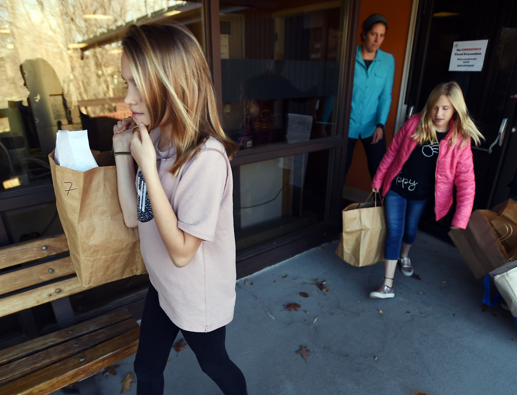 . Ellison Bonge, left, and her sister, Meredith, visiting from Shawnee, KS, help their aunt Kerry White, deliver meals on Wheel in Boulder.   Cliff Grassmick  Photographer November 22, 2017