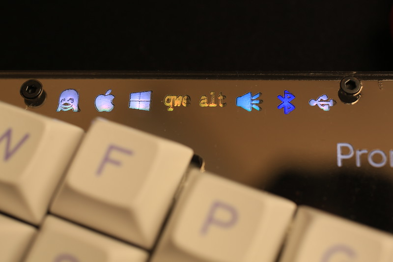 And the other side. From left to right: Linux/Apple/Windows Unicode input method, QWERTY or alternative layout, faux clicky, Bluetooth, USB.<br /> <br /> Legends are a little off here, probably caused by some problems with laser cutting.