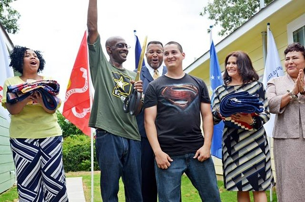 Miguel (Superman shirt) at the 2013 dedication of his Veterans Build home. He took just 7 years to pay off his mortgage to own the home outright.
