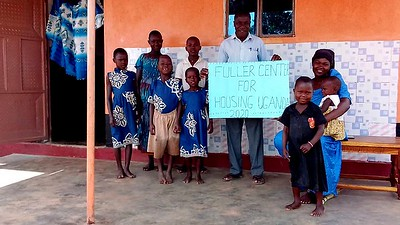 Moses Buyiinza with wife Joan and their seven children in front of their new Fuller Center home in Uganda.