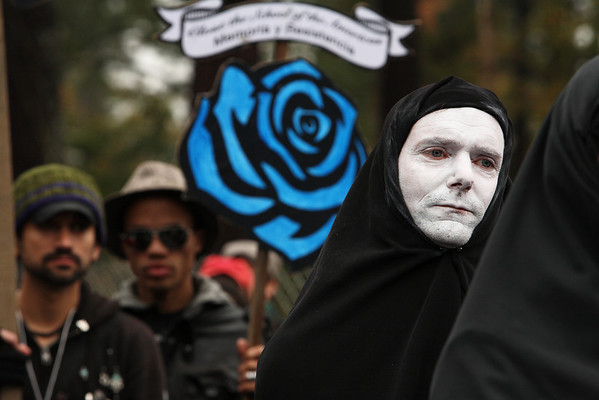 Nov 22: The annual procession is led by mourners donned in black robes.  (Photo by Linda Panetta)