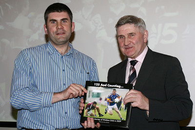Photographer Dave Barrett presents Mick O'Dwyer with the book at the launch of '125 And Counting - A Photo Journey of Wicklow GAA in 2009' in the Arklow Bay Hotel