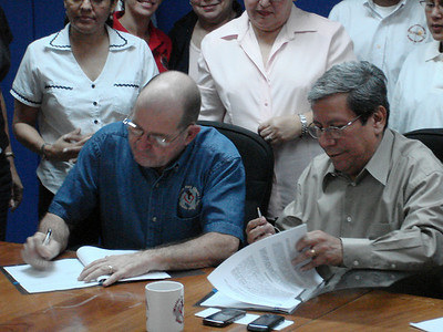 Dr. Gomez, Director of the Ministry of Health, Nicaragua and Benny Baker, Executive Director of Mision Para Cristo signing an agreement that provides for the mission to accept medicine with expired dates, have the government lab at Leon retest it and extend the shelf-life of the medicine for use in Nicaragua.