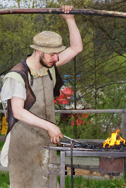 Working the bellows and holding the iron into the fire at the same time.