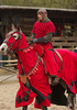 A proud knight clad in red, with black as contrast, on his proud steed.