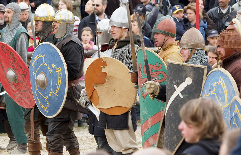 Preparing for a mass fight, both sides align themselves shield to shield.  Unlike Roman armies of the olden time, the different form of shields do allow lots and lots of space between them.<br /> <br /> On the other side, shields in warfare were much more important against incoming arrows (which happen to have right of way) than defending against swords (though of course they'd be used for that, too), and went out of use at the time weapons powerful enough to shoot through such shields became common.<br /> <br /> Again, you see the shields, for all their more-or-less fancy design, do carry signs of use and abuse.