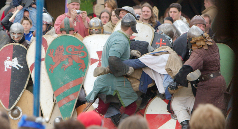 But they manage.  A squire (with a helmet) is being volunteered as a battering ram and driven several times by strong men into the shield wall.  The wall holds.