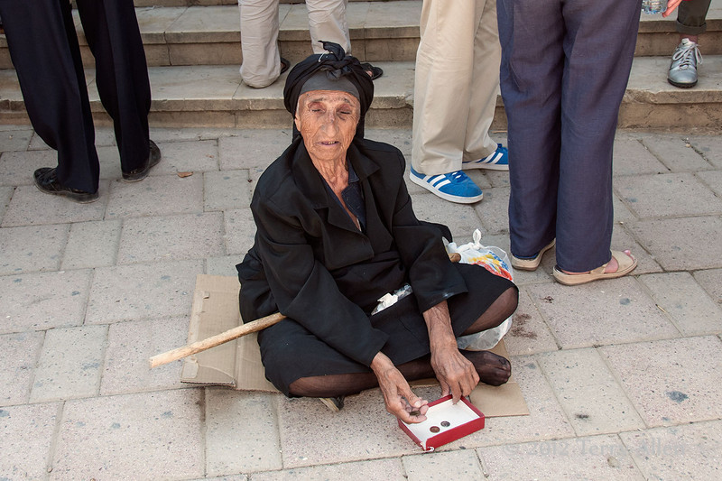 Blind-beggar-woman-with-safety-pinned-box,-Tirana,-Albania