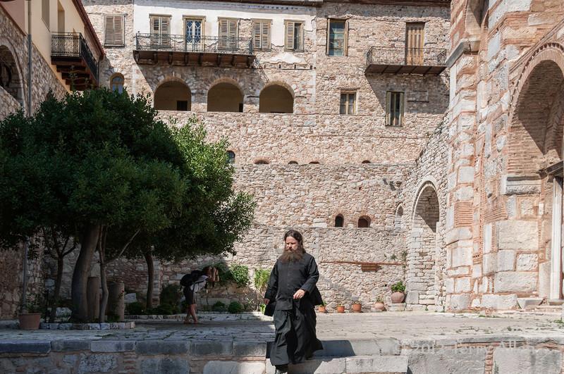 Courtyard-&-priest,Byzantine-monastery-of-Osios-Louca,-Distomo,-Greece