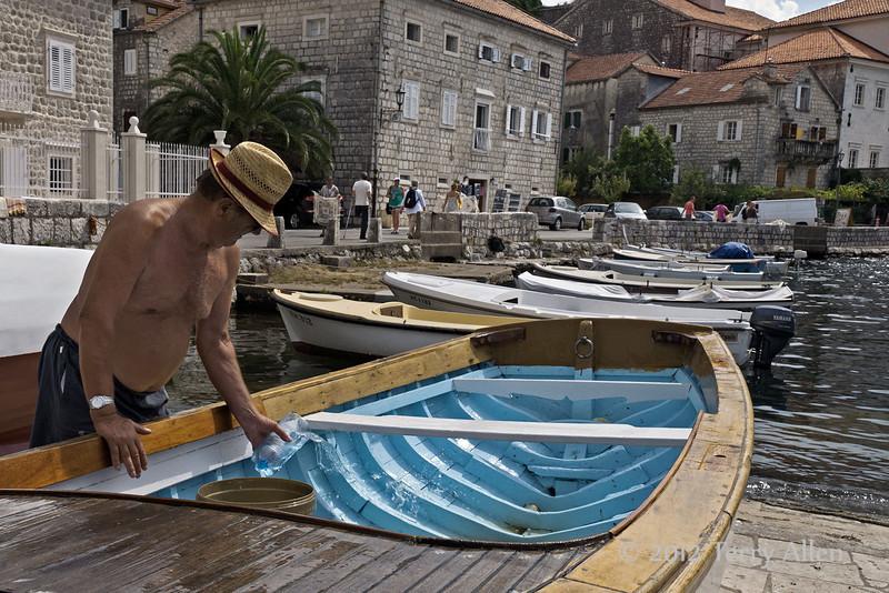 Man-washing-wooden-boat,-Perast,-Montenegro