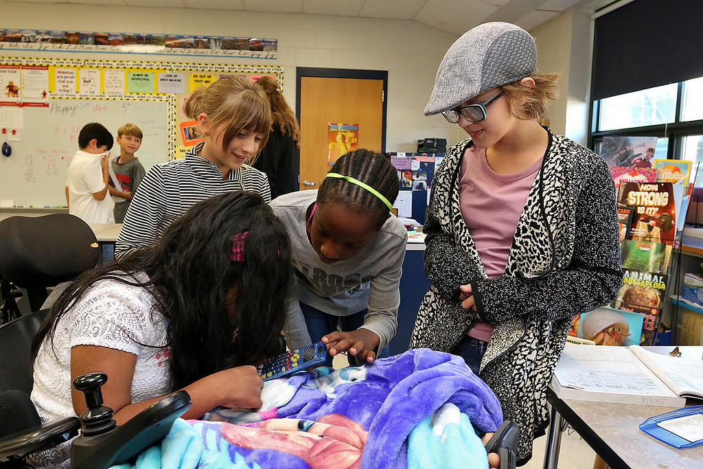 . Meera Nair, a Tyngsboro Elementary School student with cerebral palsy helps her classmates, from left, Anna Poulios, 10, Dahlya Zoua, 10, and Skyla Nichols, 10, during her visti on Tuesday, October 3, 2017. She has not been able to attend school this year due to an operation she had to have. SUN/JOHN LOVE