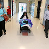Meera Nair, a Tyngsboro Elementary School student with cerebral palsy heads down the hall to see her class with her mom and dad Sindhu and Santhosh Nair on Tuesday, October 3, 2017. She had an operation that has kept her from attending school this year. SUN/JOHN LOVE