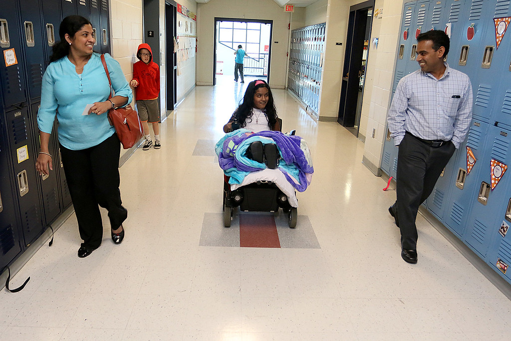 . Meera Nair, a Tyngsboro Elementary School student with cerebral palsy heads down the hall to see her class with her mom and dad Sindhu and Santhosh Nair on Tuesday, October 3, 2017. She had an operation that has kept her from attending school this year. SUN/JOHN LOVE