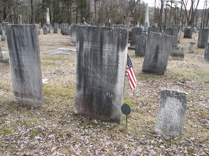 The grave of Bassett is marked with the flag. His wife's grave is to the left.