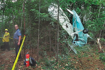 7/7/04 m.moorephoto         news---Jaffrey police officer Michael Prince on the scene of a plane crash at Silver Ranch Airpark in Jaffrey.