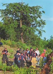 7/7/04 m.moorephoto            News---Rescue workers carry a plane crash victim out of the woods to a waiting Boston Med Flight helicopter at Silver Ranch Airpark in Jaffrey.