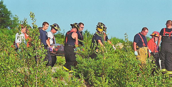 7/7/04 m.moorephoto             news---The victim of a plane crash in Jaffrey is carried on a litter to a waiting Boston Med Flight helicopter at Silver Ranch Airpark in Jaffrey.